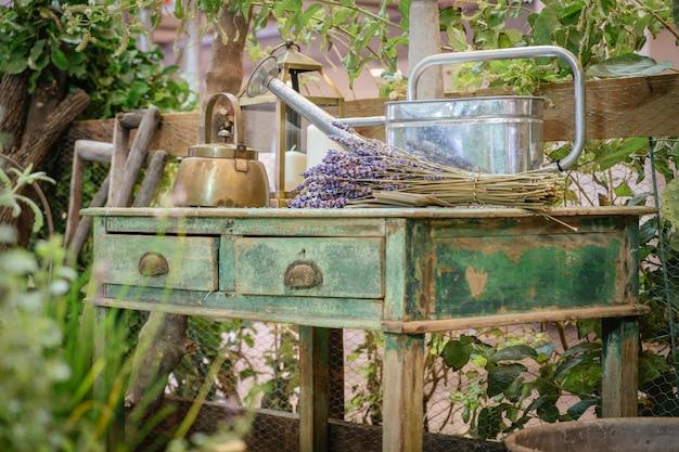Een ketel, gieter en lavendel bloemen bos op oude stijl houten groene tafel. cottage buiten tuin rustiek. Premium Foto