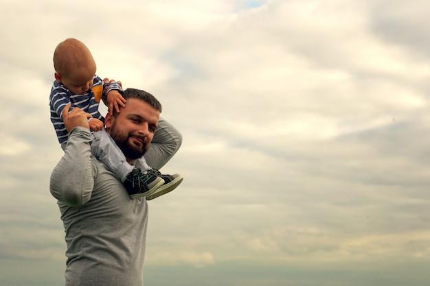 Een kind in de nek van zijn vader. loop langs het water. baby en papa tegen de hemel. Premium Foto