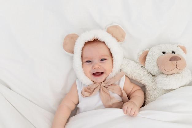 Een kind in een grappige hoed met oren met een teddybeer onder de deken. textiel en beddengoed voor kinderen. een pasgeboren baby is wakker geworden of gaat naar bed Premium Foto