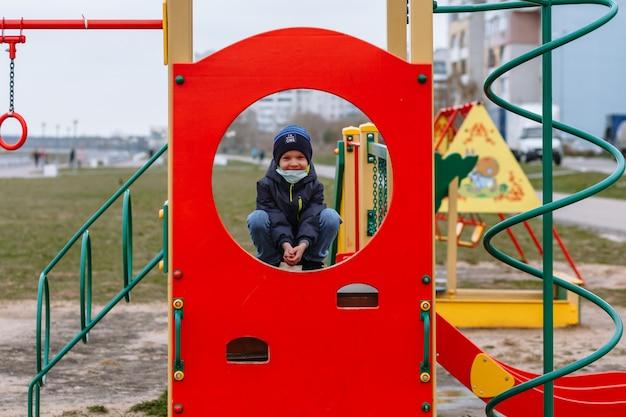 Een kind in een medisch masker dat op een speelplaats speelt Premium Foto