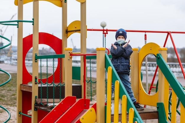 Een kind in een medisch masker met een stop-gebaar op de speelplaats Premium Foto
