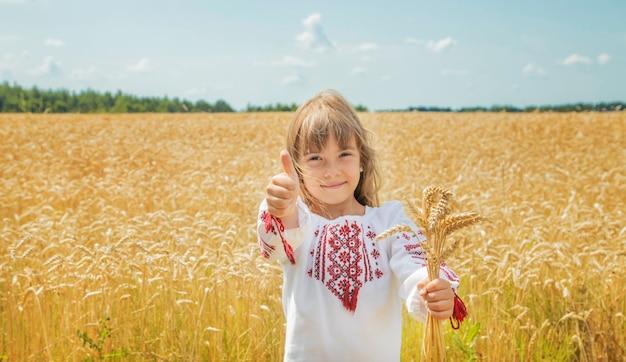 Een kind in een veld van tarwe in een geborduurd shirt. Premium Foto