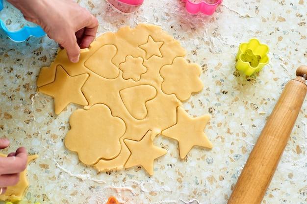 Een kind maakt koekjes, rolt het deeg uit en gebruikt vormen om koekjes te maken. Premium Foto