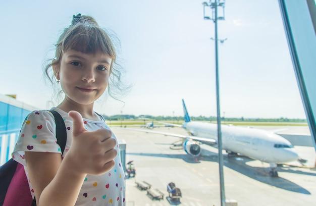 Een kind op de luchthaven op de achtergrond van het vliegtuig Premium Foto