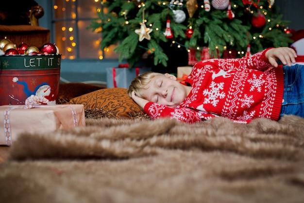 Een kind slaapt op kerstavond onder een versierde kerstboom en wacht op een geschenk. familie viert kerstmis thuis. de kinderen slapen. Premium Foto