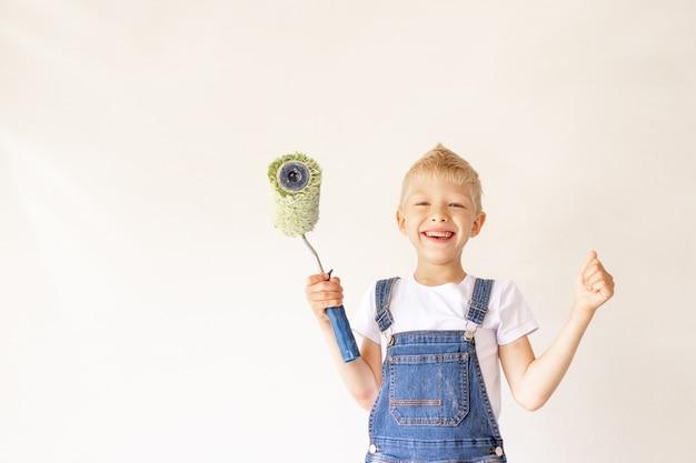Een kindbouwer in een appartement met witte muren en een roller in zijn handen toont de klas, een plek voor tekst, het concept van reparatie Premium Foto