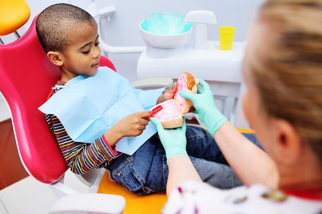 Een kindertandarts leert een afrikaans amerikaans kind dat op een tandartsstoel zit zijn tanden goed te poetsen. kindertandheelkunde Premium Foto