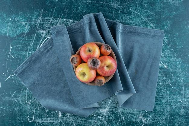 Een klein bundeltje mispelvruchten en appels in de kom, op de handdoek, op de blauwe achtergrond. hoge kwaliteit foto Gratis Foto