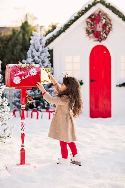 Een klein donkerbruin meisje in een beige jas en een rode lengtegraad stuurt een brief naar de kerstman in een rode brievenbus. Premium Foto