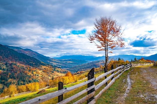 Een klein dorpje onder fantastische heuvels bedekt met kleurrijke herfstbossen in het licht van een felle warme zon bij mooi weer Premium Foto