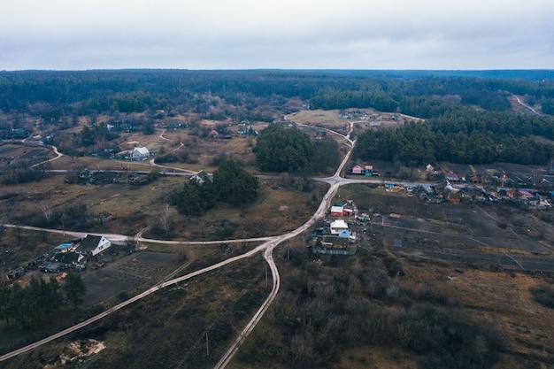 Een klein dorpje op een vlakte tussen het bos. landelijk landschap in de sneeuwloze winter. luchtfoto. Premium Foto