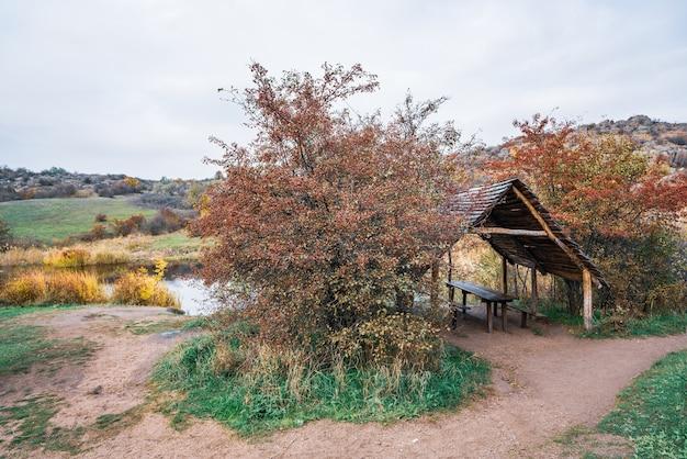 Een klein houten schattig prieel tussen prachtige herfstbomen in de natuur van de karpaten Premium Foto