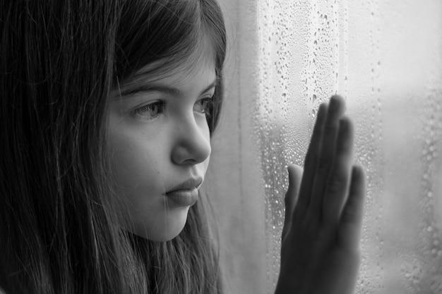 Een klein jong meisje zit bij het raam en is triest kinderproblemen eenzaamheid concept zwart-wit foto Premium Foto