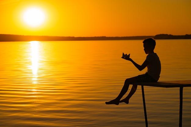 Een klein kind is op een brug met origami in de vorm van een boot in zijn handen bij zonsondergang. de benen van het kind zakken naar het water dat onder de brug stroomt Premium Foto