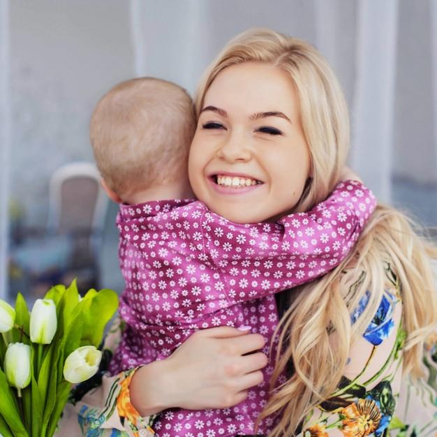 Een klein kind knuffelt moeder en geeft bloemen. het concept van jeugd, onderwijs, gezin. Premium Foto