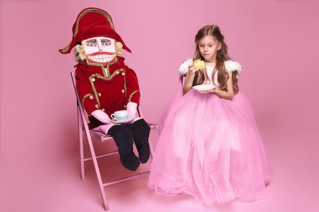Een klein meisje als schoonheid ballerina op roze lange jurk met notenkraker op roze studio met kopje thee Gratis Foto