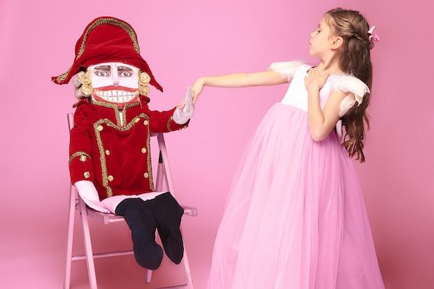 Een klein meisje als schoonheid ballerina op roze lange jurk met notenkraker op roze studio Gratis Foto