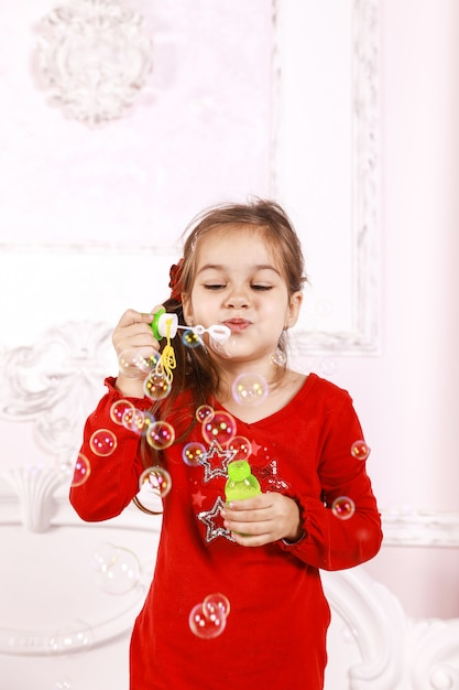 Een klein meisje gekleed in een rode pyjama speelt binnenshuis met bubbels Gratis Foto