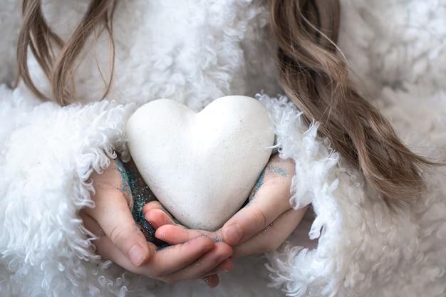 Een klein meisje heeft een hart in haar handen. Gratis Foto