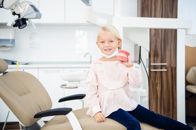 Een klein meisje houdt kunstgebit in haar hand in de tandartspraktijk Premium Foto
