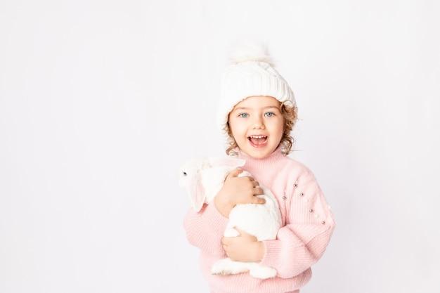 Een klein meisje in de winterkleren houdt een konijn op een witte achtergrond. nieuwjaars concept, ruimte voor tekst Premium Foto