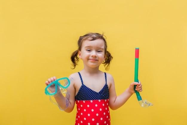 Een klein meisje in een badpak met een masker en een buis op een geel geïsoleerd Premium Foto