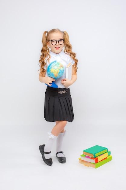 Een klein meisje in schooluniform en glazen heeft een wereldbol in haar handen op een witte achtergrond Premium Foto