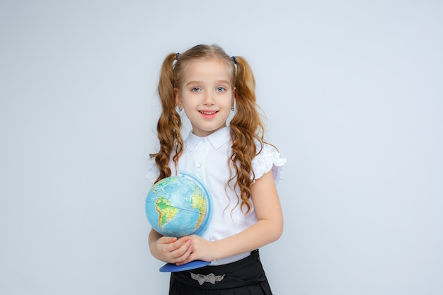 Een klein meisje in schooluniform heeft een wereldbol in haar handen op een witte achtergrond Premium Foto