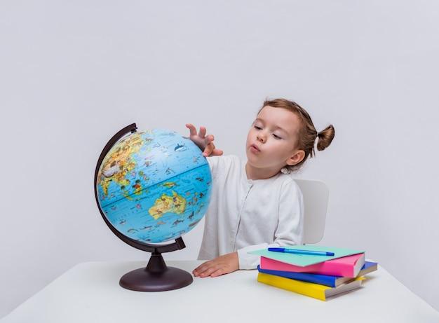 Een klein meisje leerling zit aan een tafel en bestudeert een wereldbol op een witte geïsoleerd Premium Foto