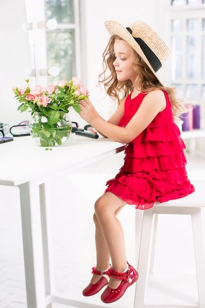 Een klein meisje met cosmetica zitten in de buurt van de spiegel. Gratis Foto