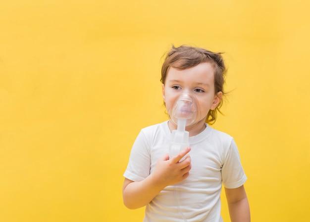 Een klein meisje met een inhalator op een gele ruimte met kopie ruimte. schattige blonde meisje met een masker op haar gezicht. opzij kijken. Premium Foto