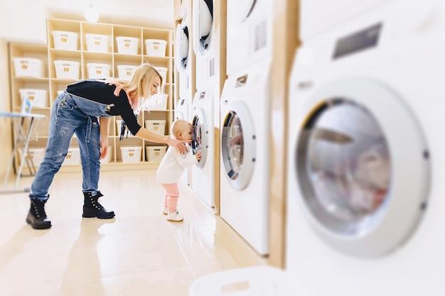 Een klein meisje met haar moeder gooit kleren in de wasmachine Premium Foto