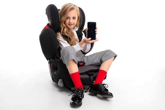 Een klein meisje met make-up en lang blond haar in een wit overhemd, rode pull-ups, broek in een kooi, rode sokken en schoenen met telefoon in een kinderstoel. Premium Foto