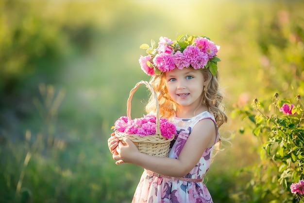 Een klein meisje met mooi lang blond haar, gekleed in een lichte jurk en een krans van echte bloemen op haar hoofd, in de tuin van een theeroos Premium Foto