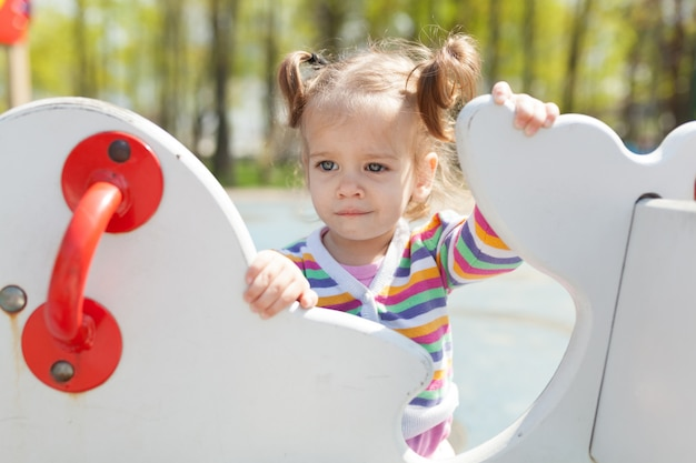 Een klein meisje met twee staarten is gekleed in een gestreepte kleurrijke jas speelt op de speelplaats Premium Foto