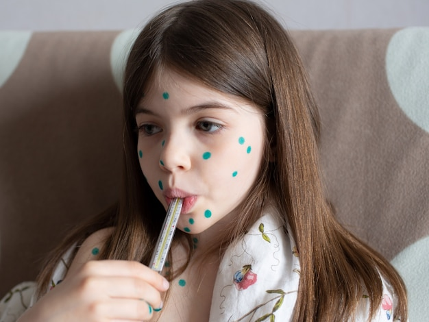 Een klein meisje met waterpokken meet haar temperatuur Premium Foto