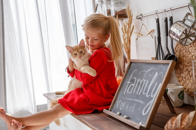 Een klein meisje speelt met een kitten in de keuken van het huis. het concept van een menselijke familie en een huisdier Premium Foto