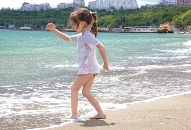 Een klein meisje staat blootsvoets aan de kust en maakt haar voeten nat in de zeegolf. Gratis Foto