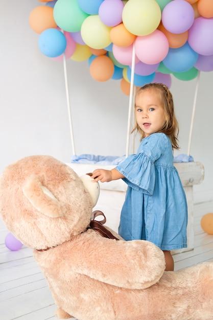 Een klein meisje viert haar verjaardag. grote teddybeer in een verjaardagscadeau. Premium Foto