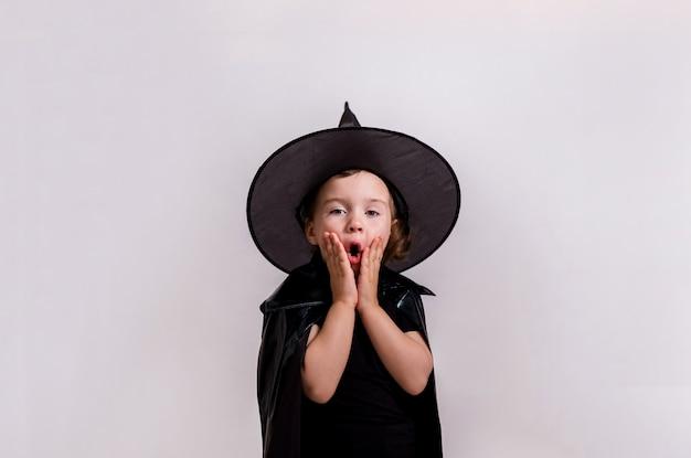 Een klein verrast meisje in heks kostuum. halloween concept Premium Foto