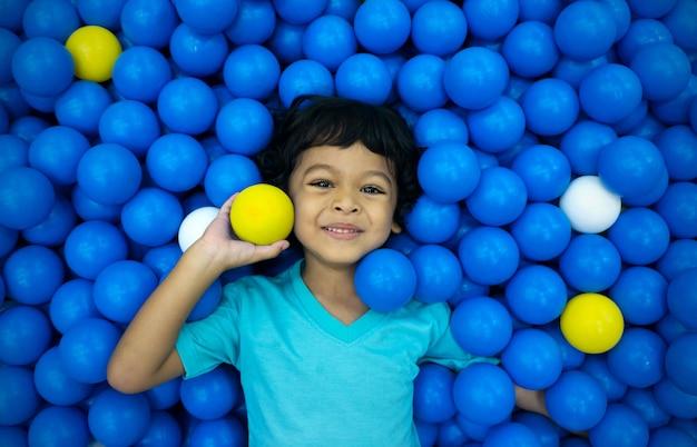 Een kleine aziatische jongen speelt met veel blauwe en gele ballen Premium Foto