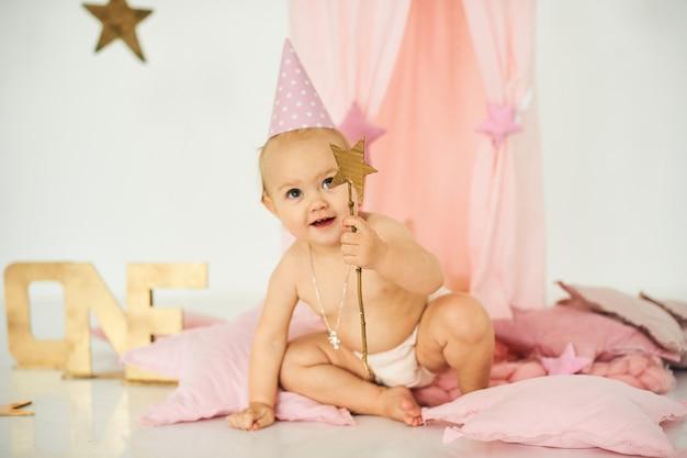 Een kleine baby in een roze tent met een toverstaf in de buurt van een grote taart. verjaardag viering concept Premium Foto