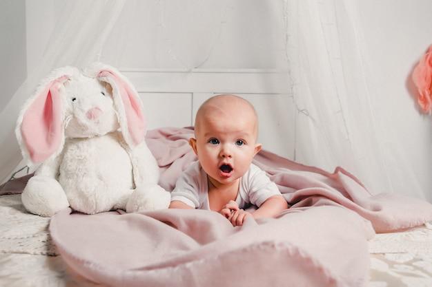 Een kleine baby legt op een bed met een speelgoedkonijn en glimlacht Premium Foto