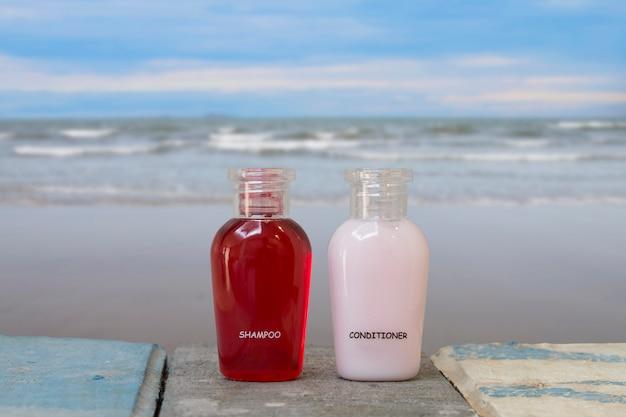 Een kleine fles shampoo en conditioner met zee op het strand. Premium Foto