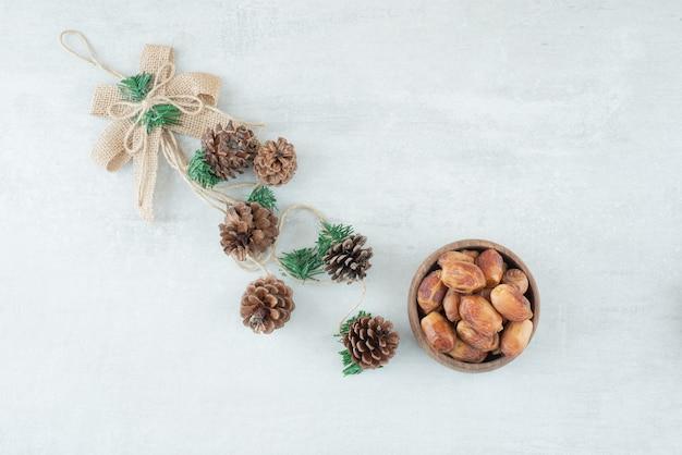 Een kleine houten kom met noten met dennenappels op witte achtergrond. hoge kwaliteit foto Gratis Foto