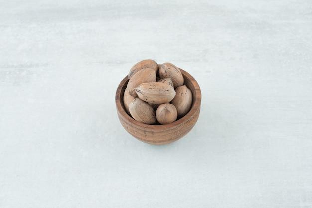 Een kleine houten kom met noten op witte achtergrond. hoge kwaliteit foto Gratis Foto