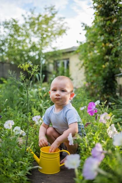 Een kleine hulpjongen zit in de tuin met een gele gieter Premium Foto