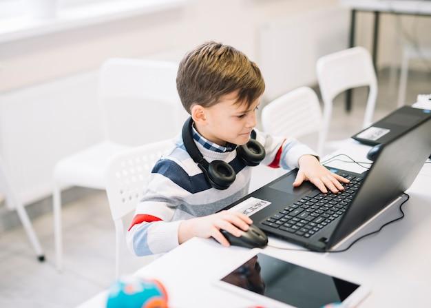 Een kleine jongen die laptop op bureau in het klaslokaal met behulp van Gratis Foto