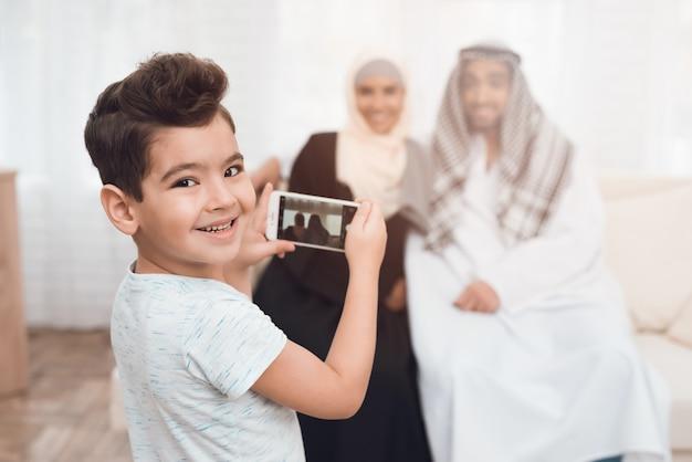 Een kleine jongen die zijn vader en moeder fotografeert. Premium Foto