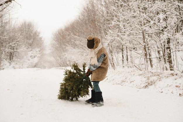 Een kleine jongen draagt een kerstboom in een elfkostuum in een besneeuwd bos. een dwerg in een bontjas sleept een boom langs een besneeuwde weg Premium Foto